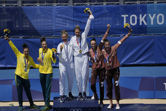 Silver medalist Mariafe Artacho del Solar, left, of Australia, and teammate Taliqua Clancy, second from left, pose with gold medalist April Ross, third from left, of the United States, and teammate Alix Klineman third from right, along with Bronze medalist Anouk Verge-Depre, second from right, of Switzerland, and teammate Joana Heidrich during the medal ceremony for women's beach volleyball at the 2020 Summer Olympics, Friday, Aug. 6, 2021, in Tokyo, Japan. (AP Photo/Petros Giannakouris)