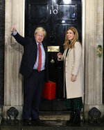 Britain's Prime Minister Boris Johnson and his partner Carrie Symonds wave from the steps of number 10 Downing Street in London, Friday, Dec. 13, 2019. Prime Minister Boris Johnson's Conservative Party has won a solid majority of seats in Britain's Parliament — a decisive outcome to a Brexit-dominated election that should allow Johnson to fulfill his plan to take the U.K. out of the European Union next month. (AP Photo/Matt Dunham)