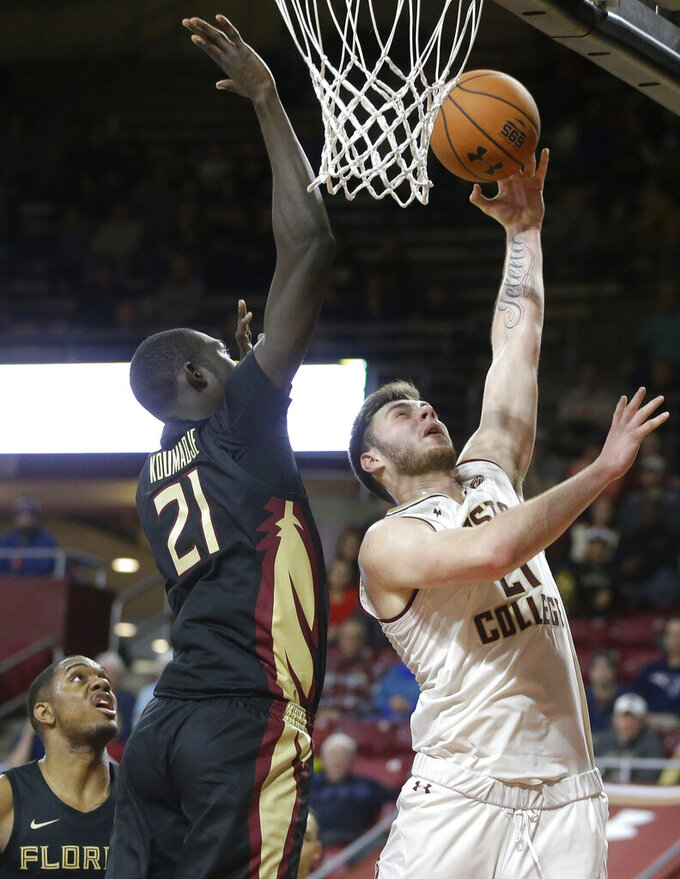 Boston College forward Nik Popovic, right, drives toward the basket past Florida State's Christ Koumadje, center left, in the second half of an NCAA college basketball game, Sunday, Jan. 20, 2019, in Boston. (AP Photo/Steven Senne)