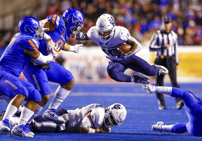 Utah State wide receiver Jordan Nathan (16) leaps over a teammate and a Boise State defender during the first half of an NCAA college football game Saturday, Nov. 24, 2018, in Boise, Idaho. (AP Photo/Steve Conner)