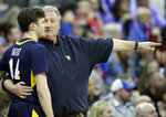West Virginia head coach Bob Huggins talks with guard Chase Harler (14) during the first half of an NCAA college basketball game in the semifinals of the Big 12 conference tournament in Kansas City, Mo., Friday, March 15, 2019. (AP Photo/Orlin Wagner)