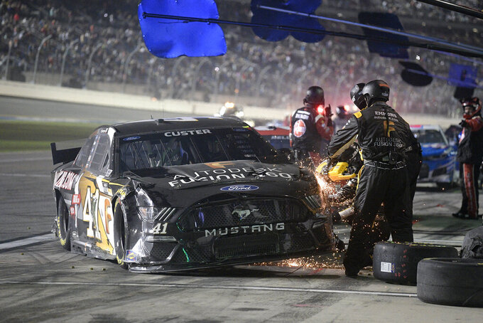Crew members work on the car driven by Cole Custer (41) on pit road during a NASCAR Cup Series auto race at Daytona International Speedway, Saturday, Aug. 28, 2021, in Daytona Beach, Fla. (AP Photo/Phelan M. Ebenhack)