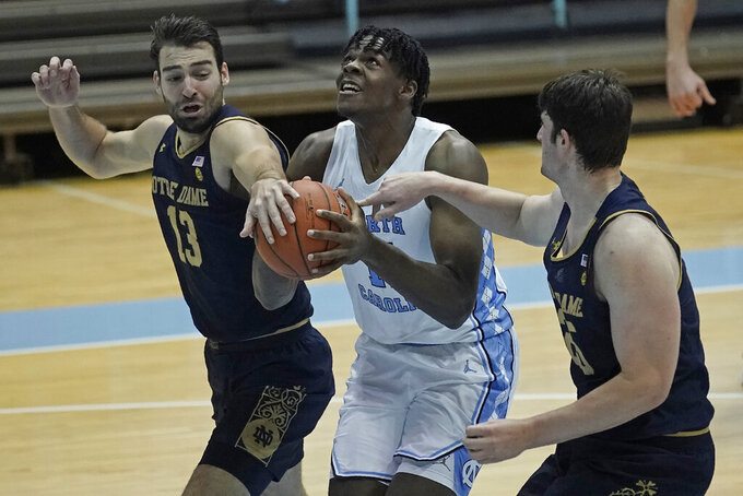 North Carolina forward Day'Ron Sharpe, center, drives between Notre Dame guard Nikola Djogo (13) and forward Matt Zona during the first half of an NCAA college basketball game in Chapel Hill, N.C., Saturday, Jan. 2, 2021. (AP Photo/Gerry Broome)