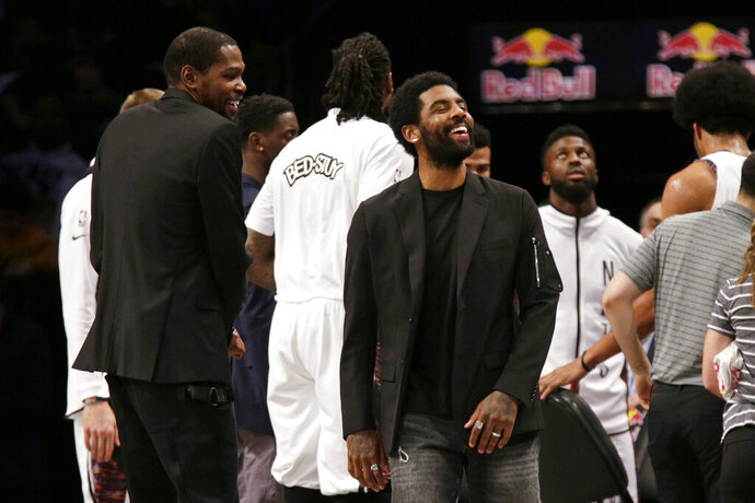 Brooklyn Nets guard Kyrie Irving, center, jokes with forward Kevin Durant, left, during a timeout against the Boston Celtics during the first half of an NBA basketball game Friday, Nov. 29, 2019, in New York. (AP Photo/Adam Hunger)