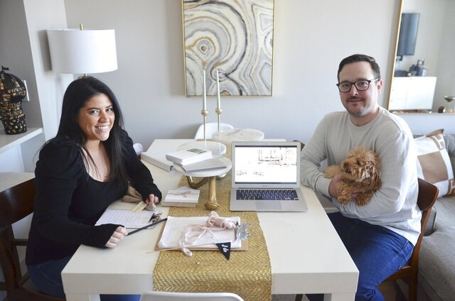 Karina L. Lopez, left, poses with her fiance Curtis Rogers and their dog Fifi at their home in the Long Island City section of the Queens borough of New York, on Saturday, April 4, 2020. The pair have long been planning their summer wedding celebration. Both have tested positive for the coronavirus, but they're continuing to plan and send out invitations to their wedding, whether it ends up being a huge party or a marriage by Zoom in their living room. (Karina L. Lopez via AP)