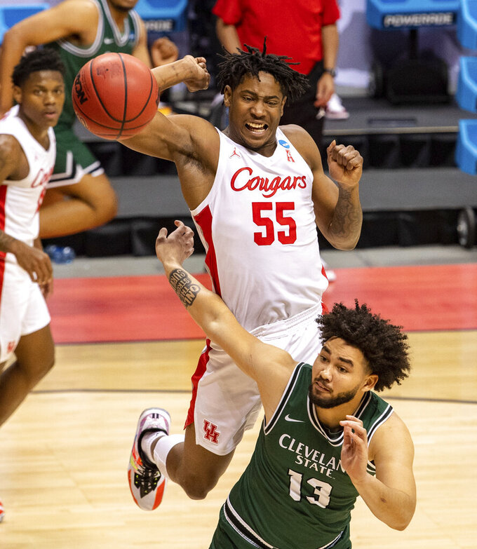Houston forward Brison Gresham (55) tries to avoid fouling Cleveland State forward Chris Greene (13) as he goes after a rebound during the second half of a first-round game in the NCAA men's college basketball tournament, Friday, March 19, 2021, at Assembly Hall in Bloomington, Ind. (AP Photo/Doug McSchooler)