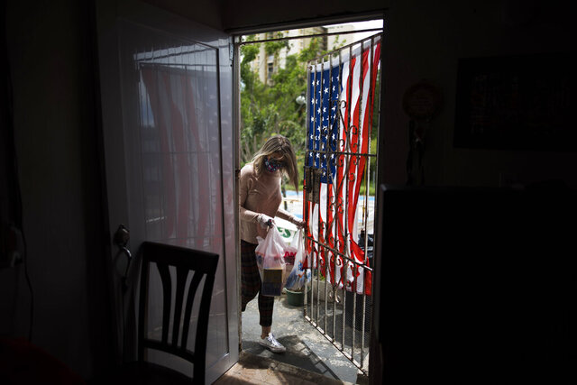 FILE - In this April 29, 2020 file photo, social worker Michelle Valentín, a former teacher, brings food to Angel Ruiz and Ivelisse Rios, a couple who are having a hard time feeding their two children while schools are closed to help contain the spread of the new coronavirus in San Juan, Puerto Rico. Puerto Rico officials announced Wednesday, May13 that they are closing more than 30 public school cafeterias and several food warehouses after dozens of workers tested positive for the new coronavirus — a blow for students who activists say are often going hungry during the pandemic lockdown. (AP Photo/Carlos Giusti, File)