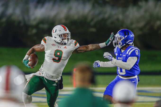 Miami tight end Brevin Jordan (9) tries to fend off Duke safety Marquis Waters (0) during the first half of an NCAA college football game Saturday, Dec. 5, 2020, in Durham, N.C. (Nell Redmond/Pool Photo via AP)