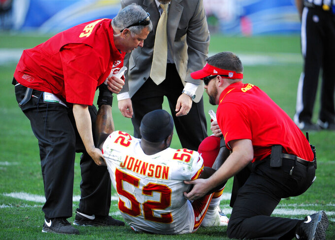FILE - In this Dec. 29, 2013, file photo, Kansas City Chiefs linebacker James-Michael Johnson is helped up after an injury while playing the San Diego Chargers during the second half in an NFL football game in San Diego. Johnson estimates he has had scores of head traumas over his dozen years of football at the high school, college and pro levels. Because of what he knows now that wasn't known when he was a kid, Johnson feels compelled to someday spell out the risks to his son, James-Michael Jr., if he wants to play football. (AP Photo/Denis Poroy, File)
