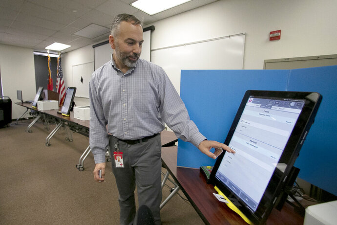 FILE- In this Sept. 16, 2019 file photo, Scott Tucker demonstrates the Dominion Voting system Georgia will use in Atlanta. Georgia secretary of state Brad Raffensperger's office confirmed the investigation into Marilyn Marks and Richard DeMillo on Wednesday, Nov. 13, 2019. Marks is the executive director of the Coalition for Good Governance and DeMillo is a cybersecurity expert and Georgia Tech professor. (AP Photo/John Bazemore, File)