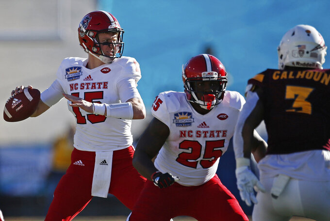 File-This Dec. 29, 2017, file photo shows North Carolina State quarterback Ryan Finley, left, throwing against Arizona State during the fist half of the Sun Bowl NCAA college football game in El Paso, Texas. Finley returned to school after flirting with entering the NFL draft after last season. (AP Photo/Andres Leighton, File)