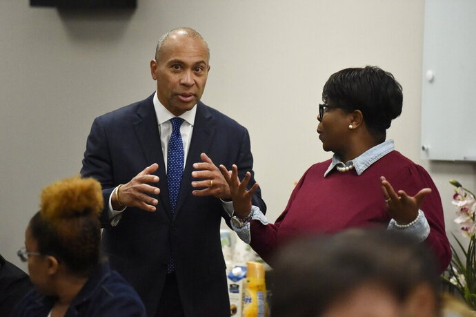 Former Massachusetts Gov. Deval Patrick, left, speaks with a business owner during a campaign stop, Tuesday, Nov. 19, 2019, in Columbia, S.C. (AP Photo/Meg Kinnard)