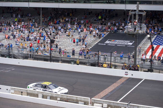 AJ Allmendinger (16) crosses the finish line as the checked flag is waved to win a NASCAR Cup Series auto race at Indianapolis Motor Speedway, Sunday, Aug. 15, 2021, in Indianapolis. (AP Photo/Doug McSchooler)