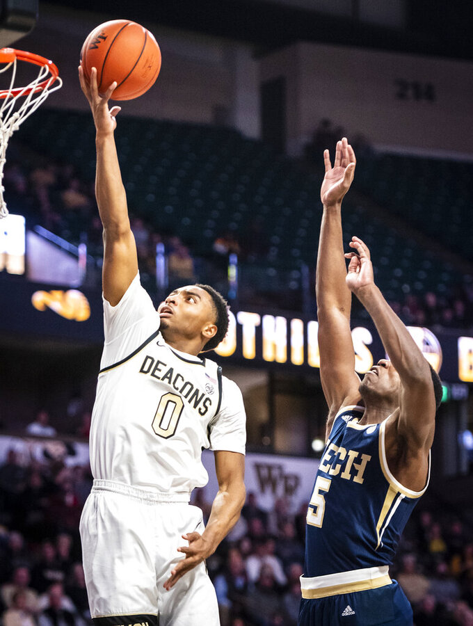 Wake Forest guard Brandon Childress (0) shoots next to a Georgia Tech player during an NCAA college basketball game Wednesday, Feb. 19, 2020, in Winston-Salem, N.C. (Andrew Dye/The Winston-Salem Journal via AP)