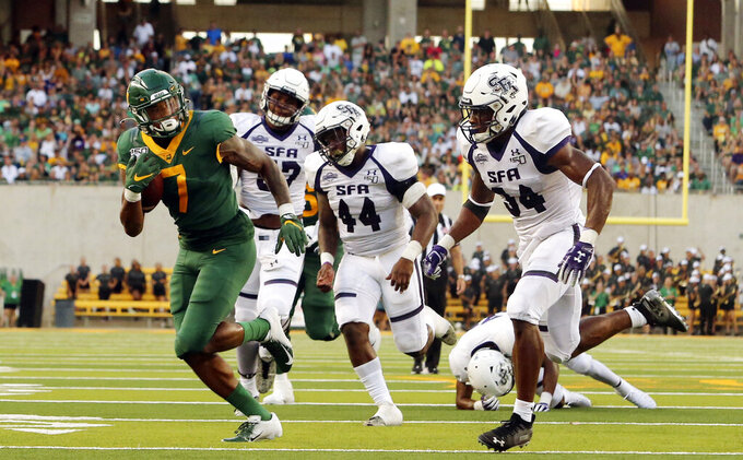Baylor running back John Lovett (7) scores past Stephen F. Austin linebacker Bert Morris (44) and safety Gavin Roland (34) in the first half of an NCAA college football game, Saturday, Aug. 31, 2019, in Waco, Texas. (Jose Yau/Waco Tribune-Herald via AP)