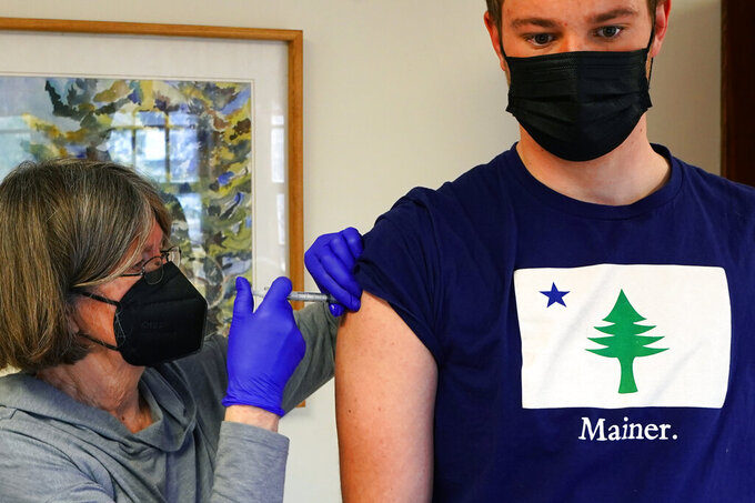 Nurse Sharon Daley administers a COVID-19 vaccination to Oliver Blank, 18, Friday, March 19, 2021, on the island of Islesford, Maine. An exemption has been made to the vaccination age restrictions to allow younger residents on remote islands to receive their shot. (AP Photo/Robert F. Bukaty)
