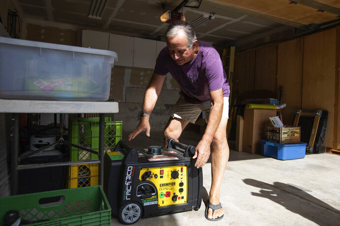 FILE - In this Tuesday, Oct. 8, 2019 file photo, Joe Wilson pulls his generator out in the garage of his home, which is in an area that is expected to lose power in the East Foothills area of San Jose, Calif. Power shutdowns intended to prevent more devastating California wildfires are raising concerns about another environmental threat: air pollution. As utilities temporarily halted service to more than 2 million people this week, many fired up standby generators that spew toxic emissions. (Randy Vazquez/San Jose Mercury News via AP, File)