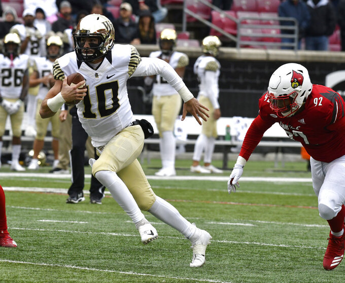 Wake Forest quarterback Sam Hartman (10) is pursued by Louisville defensive end Malik Clark as he runs through an opening during the second half of an NCAA college football game against Louisville, Saturday, Oct. 27, 2018, in Louisville, Ky. Wake Forest won 56-35. (AP Photo/Timothy D. Easley)