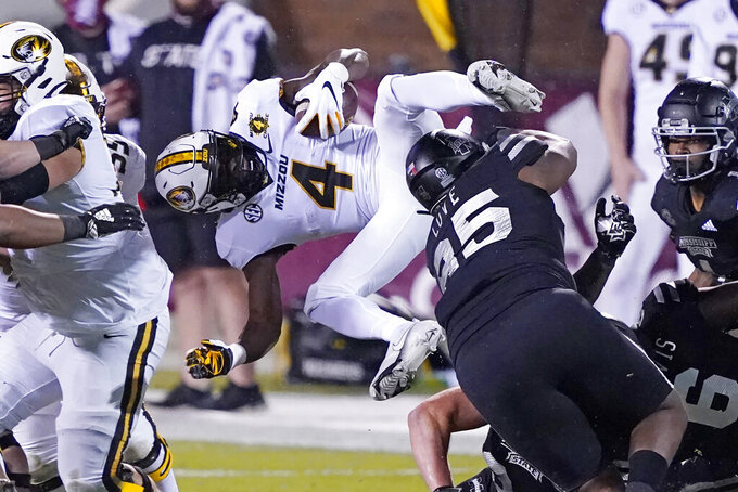 Missouri running back Elijah Young (4) is upended by Mississippi State defenders during the second half of an NCAA college football game, Saturday, Dec. 19, 2019, in Starkville, Miss. (AP Photo/Rogelio V. Solis)