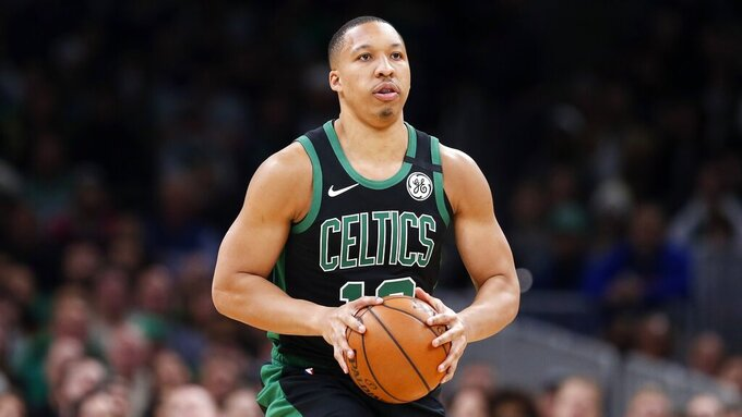 In this March, 8, 2020 photo Boston Celtics' Grant Williams plays against against the Oklahoma City Thunder during an NBA basketball game in Boston. Williams hasn't been limited to just virtual meetings with teammates during the pandemic. The rookie has been living with Boston teammate Kemba Walker, taking the All-Star point guard up on his invitation to stay with him at his home in Charlotte, N.C. not long after the league shut down in March. Williams says the company has helped him stay in shape and improve on facets of his game. He remains hopeful the NBA season will resume and believes officials will only do so if it can be done safely. (AP Photo/Michael Dwyer)