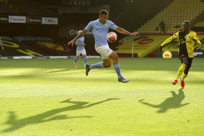 Manchester City's Gabriel Jesus, centre, controls the ball during the English Premier League soccer match between Watford and Manchester City at the Vicarage Road Stadium in Watford, England, Tuesday, July 21, 2020. (Richard Heathcote/Pool via AP)