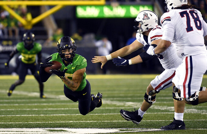 Oregon safety Bennett Williams (15) dives to make an interception in front of Arizona offensive linemen Josh McCauley (50) and Donovan Laie (78) during the first quarter of an NCAA college football game, Saturday, Sept. 25, 2021, in Eugene, Ore. (AP Photo/Andy Nelson)