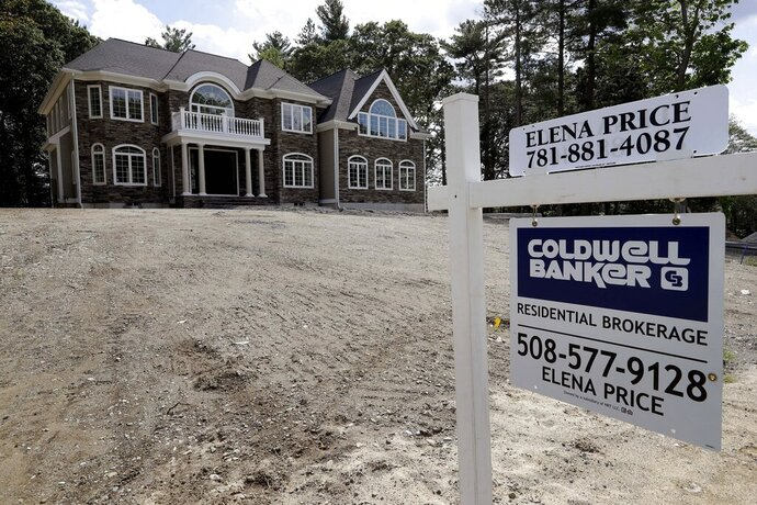 FILE - In this Sept. 3, 2019 file photo a sign rests in front of a newly constructed home, in Westwood, Mass. On Tuesday, Nov. 26, the Commerce Department reports on sales of new homes in October. (AP Photo/Steven Senne, File)
