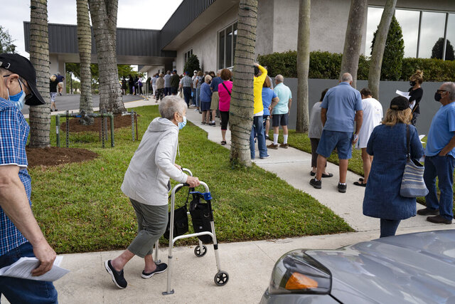 Seniors stand in line to make an appointment to receive the Moderna COVID-19 vaccine outside the King's Point clubhouse in Delray Beach,  Fla., on Wednesday, Dec. 30, 2020. (Greg Lovett /The Palm Beach Post via AP)