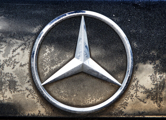 FILE - In this Wednesday, Feb. 6, 2019 file photo the logo of Daimler is photographed on a car in Frankfurt, Germany, Wednesday, Feb. 6, 2019. The maker of Mercedes-Benz luxury cars says its earnings fell by about half last year.  (AP Photo/Michael Probst, file)
