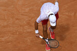 Serbia's Novak Djokovic checks his broken racket during is match with Germany's Dominik Koepfer during their quarterfinals at the Italian Open tennis tournament, in Rome, Saturday, Sept. 19, 2020. (Alfredo Falcone/LaPresse via AP)