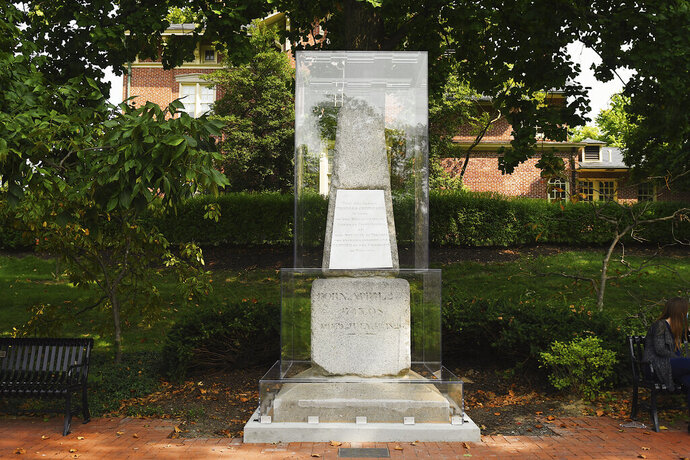 Thomas Jefferson's original granite grave marker is seen Sunday, Sept. 20, 2020, enclosed in an acrylic case on the Francis Quadrangle at the University of Missouri in Columbia, Mo. The university says it installed the $20,000 case to protect the marker, donated to the university in 1885, from vandalism amid an ongoing dispute about whether the university should honor the third president who also was a slave owner. (Madeline Carter/Columbia Daily Tribune via AP)