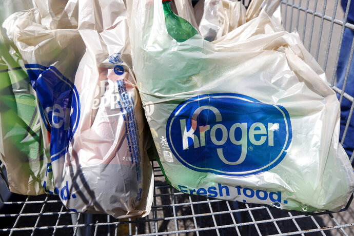 FILE - In this June 15, 2017, file photo, bagged purchases from the Kroger grocery store in Flowood, Miss., sit inside this shopping cart. A group of Instacart workers are organizing a strike across the U.S. starting Monday, March 30, 2020, to demand more pay and protection as they struggle to meet a surge in demand for grocery deliveries during the coronavirus pandemic. It was unclear how many of Instacart's shoppers - most of whom work as independent contractors - would join the strike. (AP Photo/Rogelio V. Solis, File)