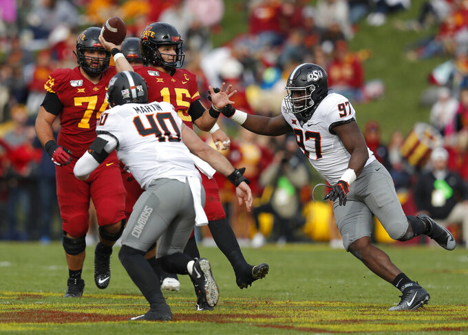 Iowa State quarterback Brock Purdy, center, tries to get off a pass as he is pressured by Oklahoma State defensive end Brock Martin(40), and Oklahoma State defensive tackle Amadou Fofana (97), during the first half of an NCAA college football game, Saturday, Oct. 26, 2019, in Ames, Iowa. (AP Photo/Matthew Putney)