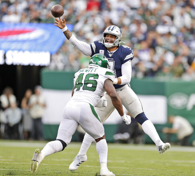 Dallas Cowboys quarterback Dak Prescott, top, is hit by New York Jets' Neville Hewitt as he throws the ball during the first half of an NFL football game, Sunday, Oct. 13, 2019, in East Rutherford, N.J. (AP Photo/Adam Hunger)