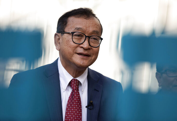 In this Nov. 4, 2019, photo, Cambodian opposition politician Sam Rainsy speaks during an interview in front of the European Parliament in Brussels. Rainsy, co-founder of the Cambodia National Rescue Party, told The Associated Press he hopes his planned return Saturday will trigger a People's Power-style movement to force Prime Minister Hun Sen from office. (AP Photo/Virginia Mayo)