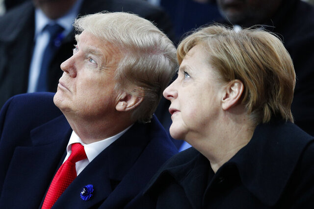 FILE - In this Sunday, Nov. 11, 2018 file photo, U.S President Donald Trump and German Chancellor Angela Merkel attend ceremonies at the Arc de Triumphe in Paris. After more than a year of thinly veiled threats that the United States could start pulling troops out of Germany unless the country increases its defense spending to NATO standards, President Donald Trump appears to be going ahead with the hardball approach with a plan to reduce the American military presence in the country by more than 25 percent. (AP Photo/Francois Mori, Pool, File)