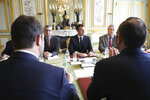 French President Emmanuel Macron, center, flanked by his cabinet director Patrick Strzoda, right, and Elysee general secretary Alexis Kohler holds a meeting with France's Premier Edouard Philippe, right back to camera, and Interior minister Christophe Castaner, left back to camera, at the Elysee presidential Palace in Paris, Monday, March 18, 2019. Macron summoned top security officials Monday after police failed to contain resurgent rioting during yellow vest protests that transformed a luxurious Paris avenue into a battle scene. (Ludovic Marin/Pool Photo via AP)