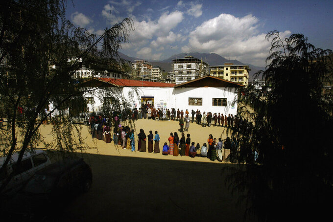 FILE- In this March 24, 2008 file photo, Bhutanese people queue up to cast their votes outside a polling station, in Thimphu, Bhutan.Bhutan's COVID-19 vaccination drive was fast from the start. As other countries rolled out their vaccination campaigns over months, Bhutan is nearly done just 16 days after it started. The tiny Himalayan kingdom has vaccinated nearly 93% of its adults. (AP Photo/Manish Swarup, File)