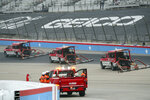 Trucks dry off the track during a red flag delay due to inclement weather during a NASCAR Cup Series auto race at Texas Motor Speedway in Fort Worth, Texas, Sunday, Oct. 25, 2020. (AP Photo/Richard W. Rodriguez)