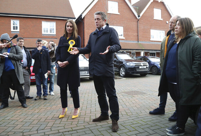 In this photo dated Saturday, Dec. 7, 2019, British actor Hugh Grant poses for a photo with Liberal Democrats Party election candidate Monica Harding, during an election campaign visit in the Esher and Walton constituency, Walton-on-Thames, England.  Hugh Grant has been on the campaign trail with the Liberal Democrats to stop Britain's Brexit from Europe and urging voters to kick Prime Minister Boris Johnson out of office when Britain goes to the polls on Dec. 12. (Gareth Fuller/PA via AP)