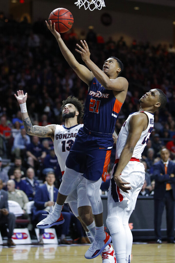 Pepperdine's Eric Cooper Jr. (21) shoots around Gonzaga's Zach Norvell Jr., right, and Josh Perkins during the second half of an NCAA semifinal college basketball game at the West Coast Conference tournament, Monday, March 11, 2019, in Las Vegas. (AP Photo/John Locher)