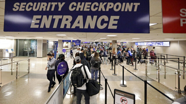 FILE - In this Wednesday, Nov. 27, 2019 file photo, Travelers walk through a security checkpoint in Terminal 2 at Salt Lake City International Airport in Salt Lake City. The Homeland Security Department is backing away from requiring U.S. citizens to submit to facial-recognition technology when they leave or enter the country. The department said Thursday, Dec. 5, 2019 that it has no plans to expand facial recognition to U.S. citizens. A spokesman said DHS will delete the idea from its regulatory agenda, where privacy advocates spotted it this week  (AP Photo/Rick Bowmer, File)