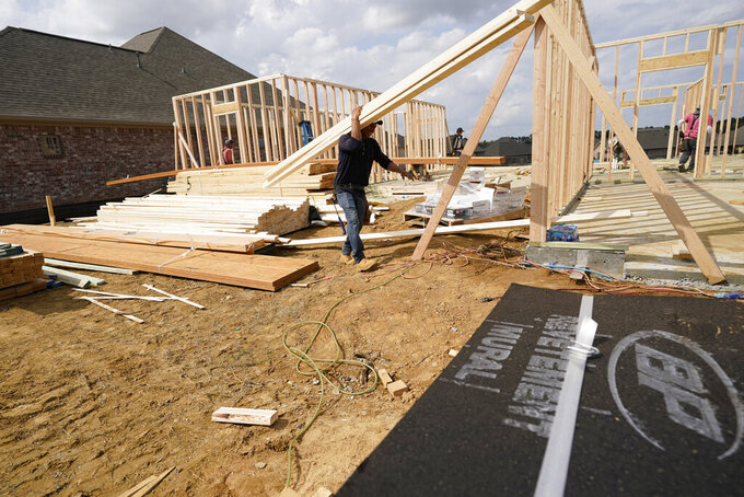 A workman carries beamS at a new housing site in Madison County, Miss., Tuesday, March 16, 2021.  U.S. construction spending fell in February after several months of steady gains, likely because of unseasonably cold weather and winter storms in the south. The Commerce Department said Thursday, April 1,  that spending on building projects slipped 0.8% in February, after a 1.2% gain in January.  (AP Photo/Rogelio V. Solis)