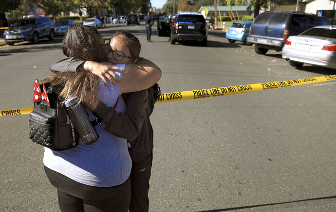 Xiomara Martinez, left, embraces her sister Alondra Moya after Moya and other students were released from a lockdown after a student of Ridgewway High School in Santa Rosa, Calif., was arrested for shooting another student across from the high school Tuesday, Oct. 22, 2019. (Kent Porter/The Press Democrat via AP)