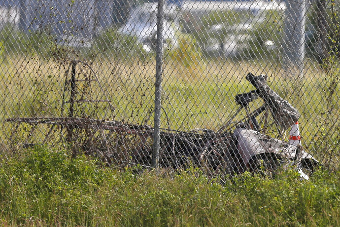 The charred wreckage of a private plane is seen in a field near the Industrial Canal and New Orleans Lakefront airport, in New Orleans, Friday, Aug. 16, 2019. The city said on its