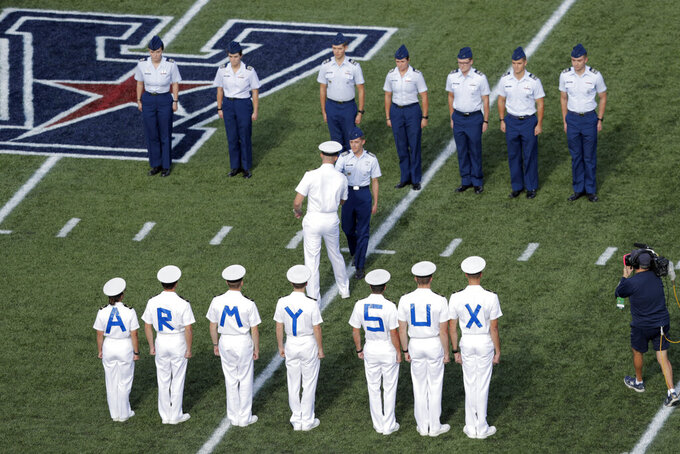 Navy students, bottom, wear a message on their backs as they greet Air Force students on the field prior to an NCAA college football game Saturday, Oct. 5, 2019, in Annapolis, Md. (AP Photo/Julio Cortez)