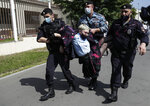 Police officers detains a protester, center, dressed as a Russian police officer before a court hearing of the New Greatness group who are charged with the organization of an extremist association in Moscow, Russia, Thursday, Aug. 6, 2020. Arrests of the two youngest members of the New Greatness group - 17-year-old Anna Pavlikova and 19-year-old Maria Dubovik - prompted a mass protest in August 2018, after which the two teenagers were released under house arrest. (AP Photo/Pavel Golovkin)
