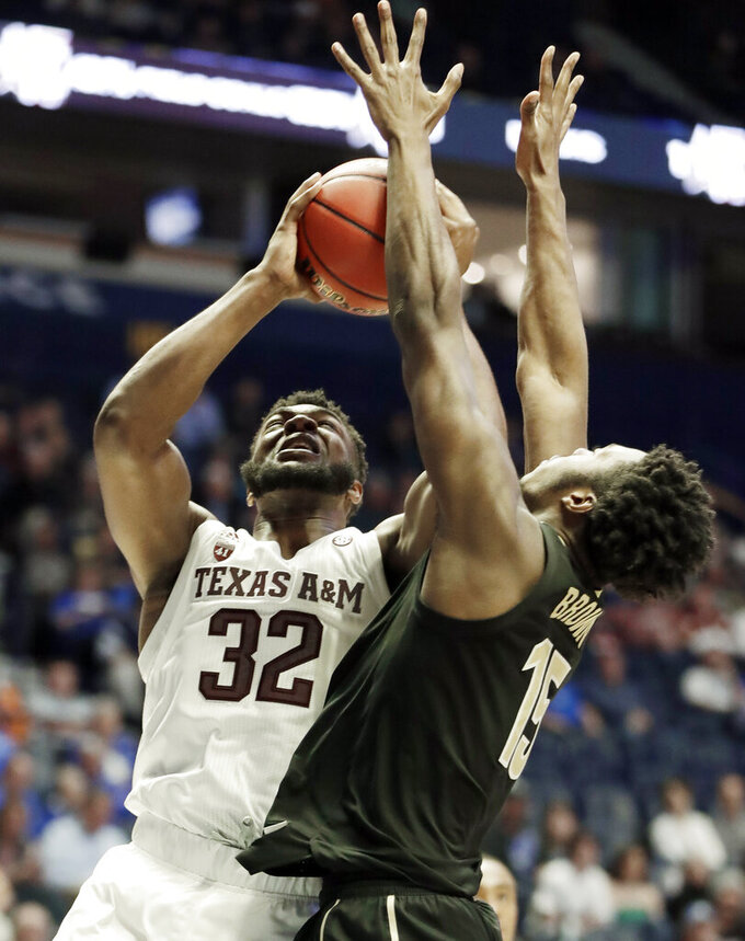 Texas A&M forward Josh Nebo (32) shoots against Vanderbilt forward Clevon Brown (15) in the second half of an NCAA college basketball game at the Southeastern Conference tournament, Wednesday, March 13, 2019, in Nashville, Tenn. Texas A&M won 69-52. (AP Photo/Mark Humphrey)