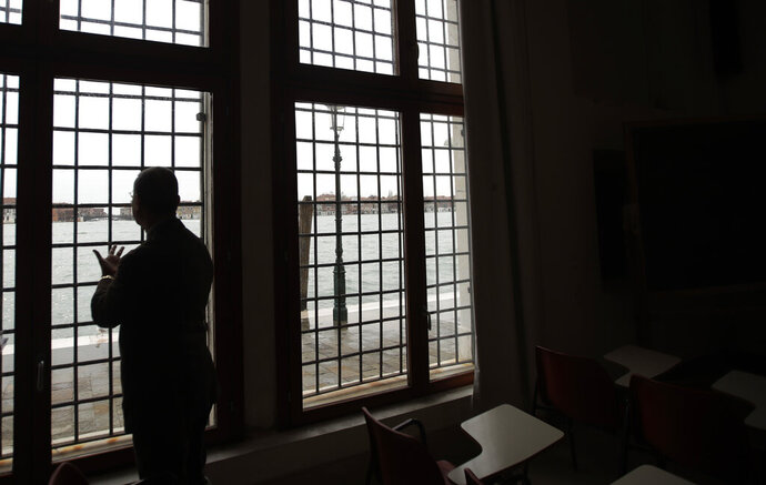 In this photo taken on Saturday, Nov. 16 2019, Fabio Moretti, president of the Accademia di Belle Arti, Fine Arts Academy, looks out of a window of the academy during an interview with the Associated Press, in Venice, Italy. Venetians are fed up with what they see as an inadequate to the city's mounting problems: record-breaking flooding, damaging cruise ship traffic and over-tourism. They feel largely left to their own devices, and with ever fewer Venetians living in the historic part of the city to defend its interests and keep it from becoming a theme park or museum. (AP Photo/Luca Bruno)