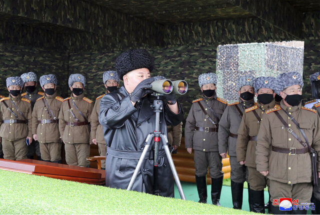 FILE - In this Friday, Feb. 28, 2020, file photo provided on Feb. 29, 2020 by the North Korean government, North Korean leader Kim Jong Un, center, inspects the military drill of units of the Korean People's Army, with soldiers shown wearing face masks. South Korea's military says North Korea has fired at least one unidentified projectile. The launch on Monday, March 2, 2020 came two days North Korea's state media said leader Kim supervised an artillery drill aimed at testing the combat readiness of units in front-line and eastern areas. Independent journalists were not given access to cover the event depicted in this image distributed by the North Korean government. The content of this image is as provided and cannot be independently verified. Korean language watermark on image as provided by source reads: